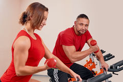 Indoor bycicle cycling in gym. Happy couple doing indoor biking in a fitness club Stock Photos