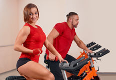 Indoor bycicle cycling in gym. Happy couple doing indoor biking in a fitness club Royalty Free Stock Image