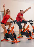 Indoor bycicle cycling in gym. Happy couple doing indoor biking in a fitness club Stock Photography