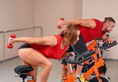 Indoor bycicle cycling in gym. Happy couple doing indoor biking in a fitness club Stock Photo