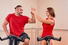Indoor bycicle cycling handshake. Happy couple portrait indoor handshake. biking in a fitness club Stock Images