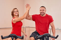 Indoor bycicle cycling portrait. Happy couple portrait indoor biking in a fitness club Royalty Free Stock Photo