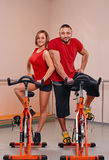 Indoor bycicle cycling portrait. Happy couple portrait indoor biking in a fitness club Stock Image