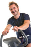 Indoor cardio training with spinning bike. Man sitting on spinning bicycle and is doint cardio training with a spinning bike. Isolated on white background Stock Photo