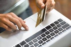 使用膝上型计算机和信用卡indoor.close-up手的妇女 库存照片