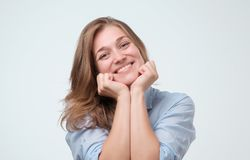 Indoor close up shot of young attractive european woman, smiling warmly and friendly while listening to you royalty free stock photography