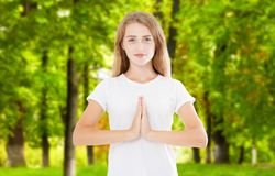 Indoor closeup of beautiful European woman in white T-shirt isolated on park background practicing yoga and meditation stock images