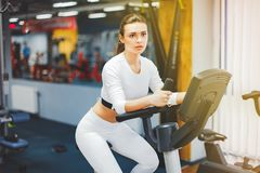 Indoor cycling woman doing cardio workout biking on indoors gym bike. Indoor cycling woman doing HIT cardio workout biking on indoors gym bike. Girl cyclist Royalty Free Stock Photos