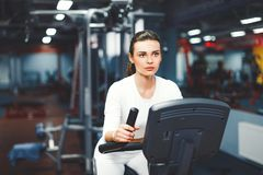 Indoor cycling woman doing cardio workout biking on indoors gym bike. Indoor cycling woman doing HIT cardio workout biking on indoors gym bike. Girl cyclist Royalty Free Stock Images