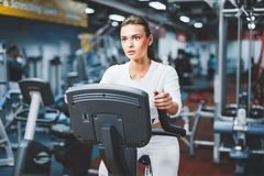 Indoor cycling woman doing cardio workout biking on indoors gym bike. Indoor cycling woman doing HIT cardio workout biking on indoors gym bike. Girl cyclist Royalty Free Stock Photo