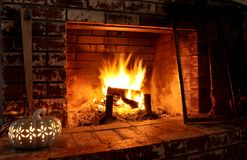 Indoor Fireplace with cozy fire. Indoor fire with fall holiday items Royalty Free Stock Photos