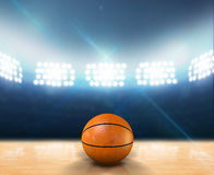Indoor Floodlit Basketball Court. An indoor basketball court with an orange ball on an unmarked wooden floor under illuminated floodlights royalty free stock image