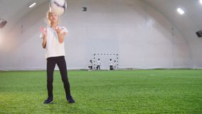 Indoor football arena. A little girl playing with a ball. Throwing it up. Portrait stock video