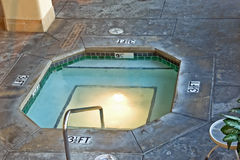 An indoor jacuzzi. A large built in jacuzzi on the ground of a great hall with stone tiles is illuminated by both the window light and lamps Stock Images