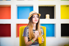 Indoor lifestyle portrait of beautiful woman posing at cafe, drinking fresh healthy tasty juice, smiling, have nice time. Royalty Free Stock Photo
