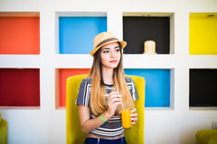 Indoor lifestyle portrait of beautiful woman posing at cafe, drinking fresh healthy tasty juice, smiling, have nice time. Stock Photos