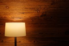 Indoor lighting by floor lamp at wooden wall royalty free stock image