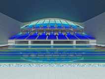 Indoor Olympic size swimming pool arena with blue seats Stock Photos