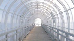 Indoor pedestrian overpass with a semi-circular ceiling made of plastic. Using plastic translucent blue sky stock footage