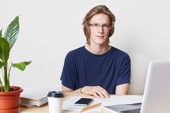 Indoor picture of talented professional male office worker with trendy hairstyle, wears spectacles and t shirt, sits at table, wor. Ks with documents, laptop Stock Photo
