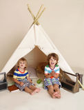 Indoor Play with Teepee Tent. Children, kids playing at home indoors in a teepee tent Royalty Free Stock Images