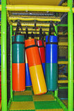 Indoor playground playthings. Colorful punching bag cylinders hanging in indoor play area for kids Stock Photography