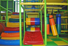 Indoor playground playthings. Colorful punching bag cylinders and padded stairs in indoor play area for kids Stock Photography