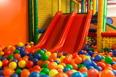 Indoor playground slides. Indoor children playground in arena with slides and colorful balls Royalty Free Stock Photo