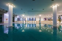 Indoor pool in the hotel, chaise lounges stock images