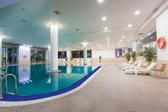 Indoor pool in hotel, sun loungers and orange life ring weighs royalty free stock photos