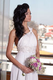 Indoor portrait of adorable bride with black long hair in front of window. Stock Images