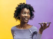 Indoor portrait of attractive young black woman holding blank smartphone royalty free stock photography