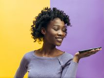 Indoor portrait of attractive young black woman holding blank smartphone stock image