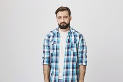 Indoor portrait of bearded man with gloomy smile, looking miserably at camera, standing against gray background. Nobody. Greet him person on his birthday Royalty Free Stock Photo