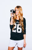 Indoor Portrait of beautiful blonde young woman holding vintage 8mm camera. Warm color. Royalty Free Stock Photos