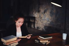 Indoor portrait of beautiful redhead woman learning or reading books in university. Or library Royalty Free Stock Photos
