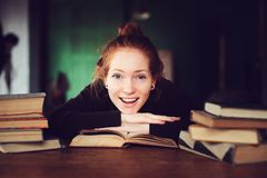 Indoor portrait of beautiful redhead woman learning or reading books in university. Or library Royalty Free Stock Image