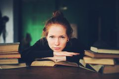 Indoor portrait of beautiful redhead woman learning or reading books in university. Or library Stock Photos