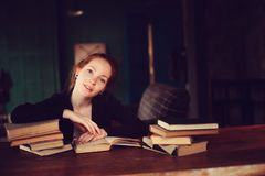 Indoor portrait of beautiful redhead woman learning or reading books in university. Or library Royalty Free Stock Photography
