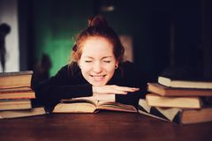 Indoor portrait of beautiful redhead woman learning or reading books in university. Or library Stock Photography