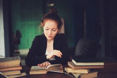 Indoor portrait of beautiful redhead woman learning or reading books in university. Or library Royalty Free Stock Photo