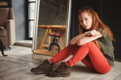 Indoor portrait of beautiful young redhead woman. Dressed in hipster style Stock Images