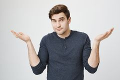 Indoor portrait of confused handsome guy showing I have no idea gesture, shrugging shoulders and raising hands, standing. Against gray background. Sorry I did stock photography