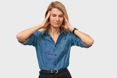 Indoor portrait of exhausted young female touching her head with closed eyes posing on white studio background stock photos