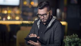 Indoor portrait of a handsome guy with beard working on tablet in cafe, big eating space, fantasctic interior. stock video