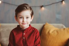Indoor portrait of happy handsome stylish child boy sitting on cozy couch. In casual clothing royalty free stock photo
