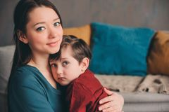 Indoor portrait of happy loving mother comforting toddler son at home. Casual lifestyles of modern family stock image