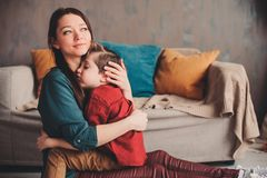 Indoor portrait of happy loving mother comforting toddler son at home. Casual lifestyles of modern family royalty free stock photo