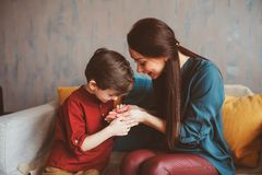 Indoor portrait of happy mother and child son sitting on couch and playing royalty free stock photo