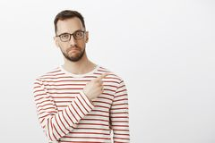 Indoor portrait of impressed good-looking mature guy in eyewear, pointing at upper right corner and making not bad stock photos